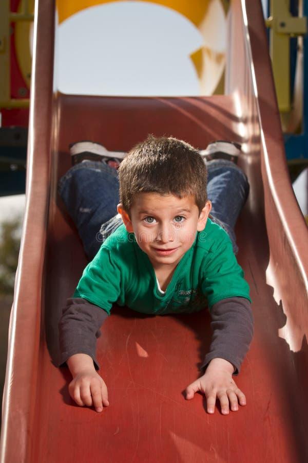 Boy on slide. Boy with blue eyes on slide royalty free stock photo