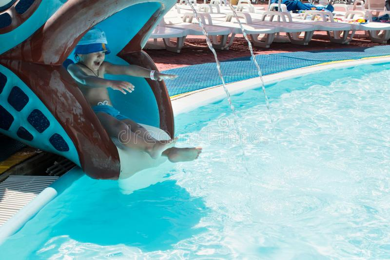 A boy slides on a water slide into the pool. The boy in the panama slides on a water slide in the form of fish in the pool with blue water royalty free stock images