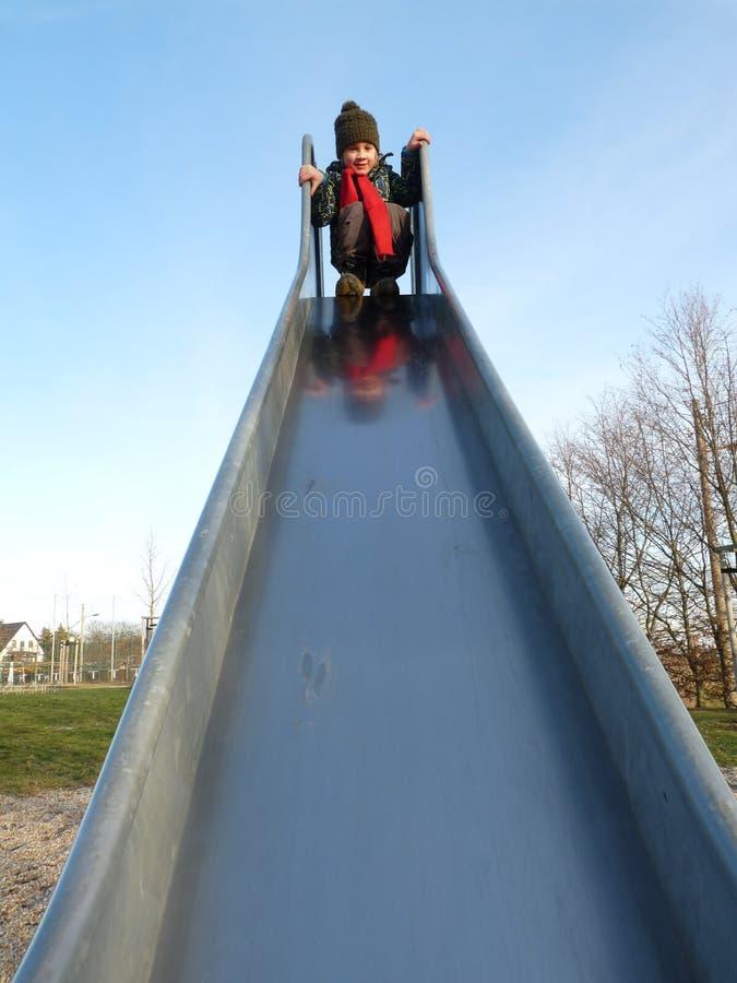A boy sliding down the chute stock photos