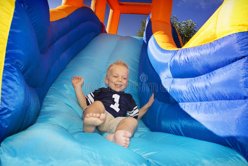 Boy sliding down an inflatable Slide royalty free stock images