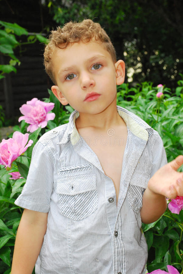 Boy smelling a peony. stock photography