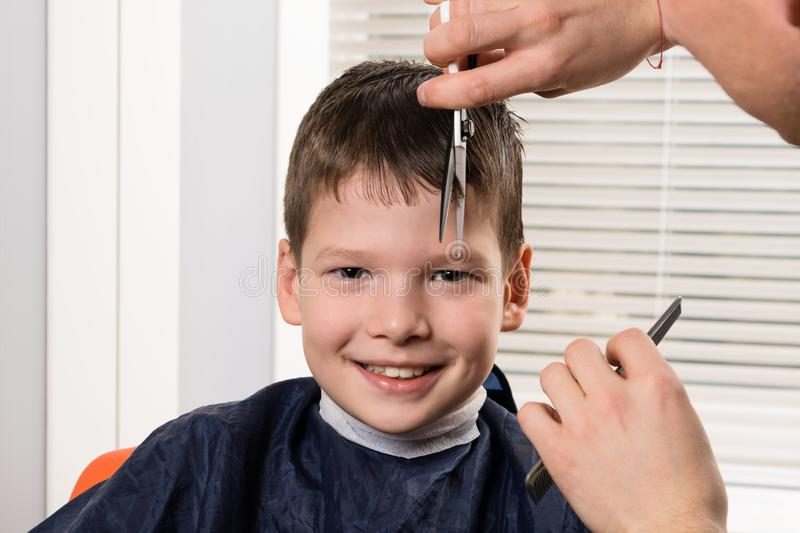 The boy smiles, the master stylist cuts his hair with scissors royalty free stock photos