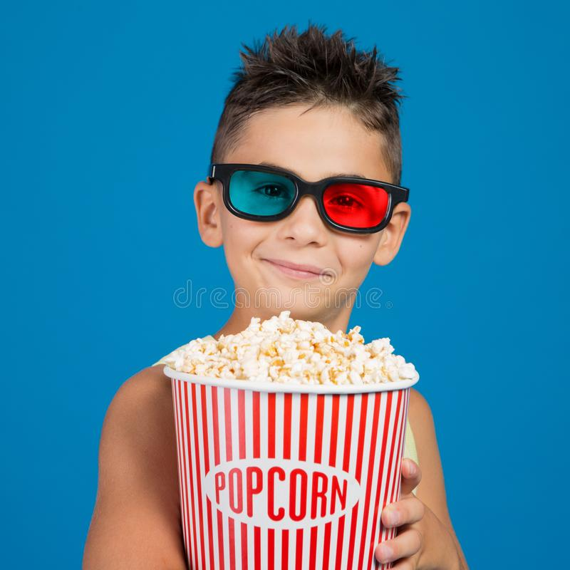 Boy smiling in 3d glasses, with a bucket of popcorn, concept of cinema and entertainment stock images