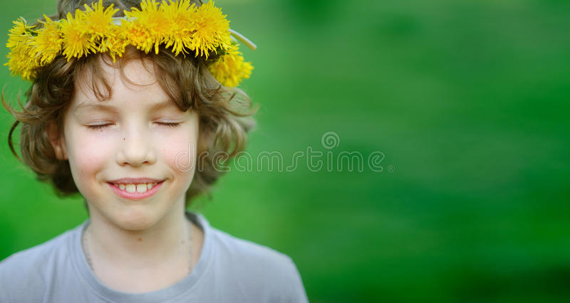 Boy smiling, with eyes closed and wreath on his head royalty free stock photos