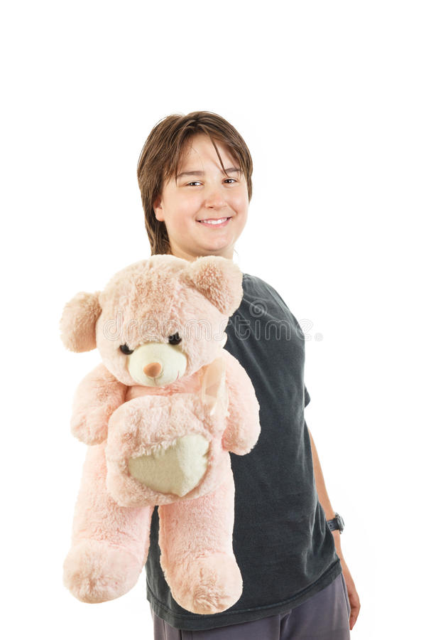 Boy smiling and holding teddy bear toy as gift for girl stock photography