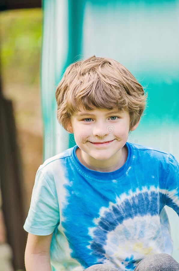 Boy smiling outside on a slide on summer on a sunny day royalty free stock photos