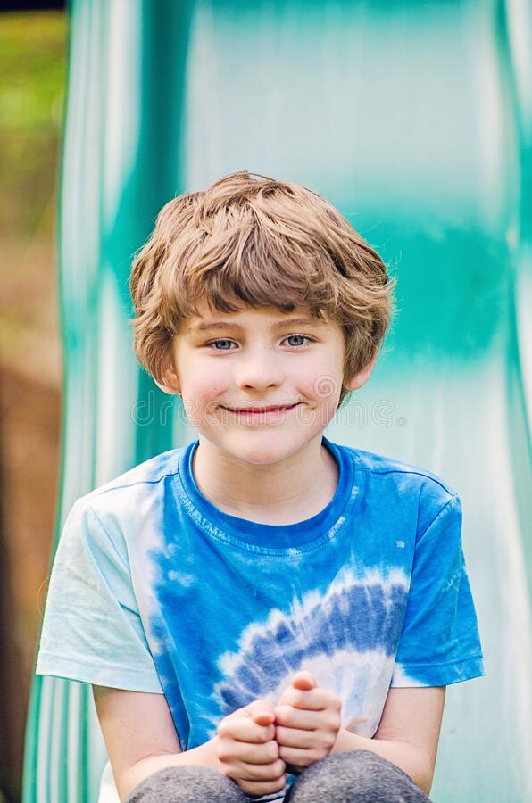 Boy smiling outside on a slide on summer on a sunny day stock images