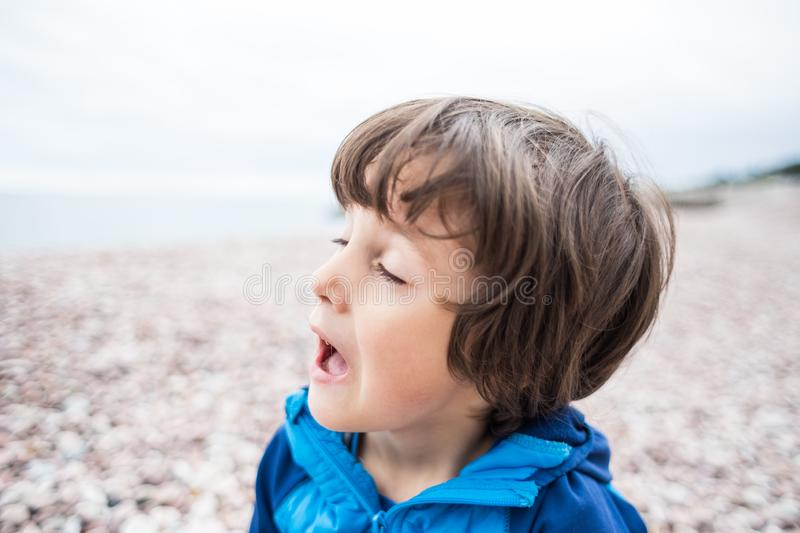 The boy is sneezing. The baby is yawning. The kid sits near the sea and accidentally begins to sneeze royalty free stock photography