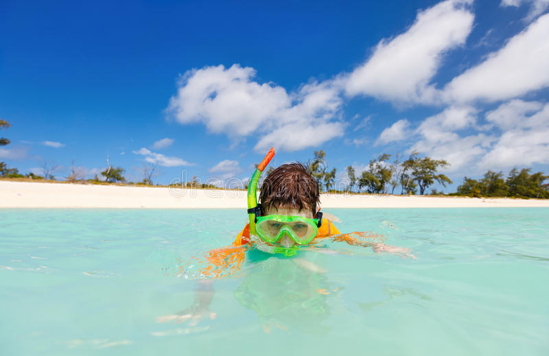 Boy snorkeling. Happy boy with snorkeling mask in turquoise tropical ocean water royalty free stock images