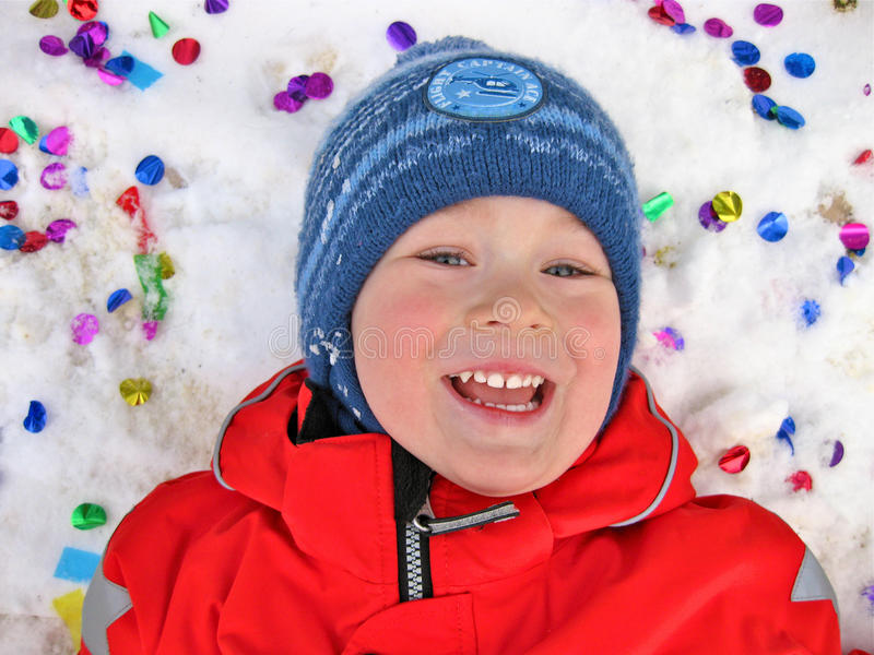 Boy in the snow and confetti. Little boy is lying in the snow and confetti royalty free stock images
