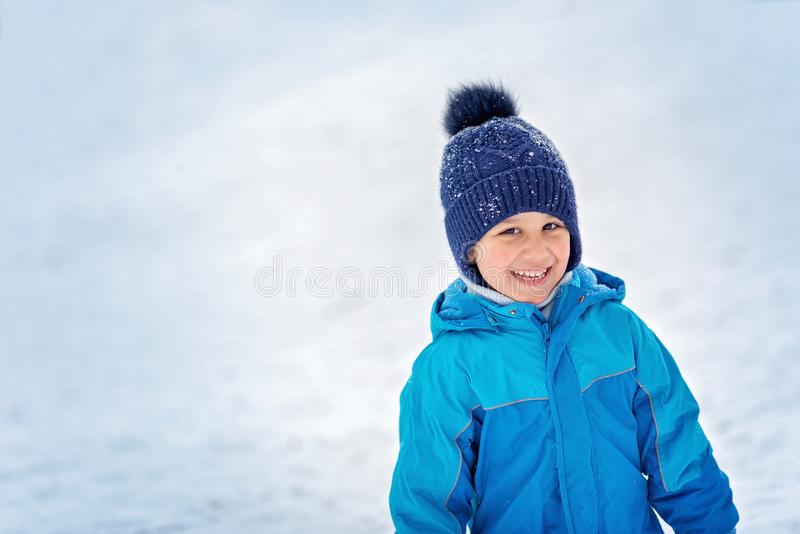 Boy in snow in Park. boy plays in winter wood. Adorable child having fun in winter park. playing outdoors with snow. Active activity attractive baby casual royalty free stock image
