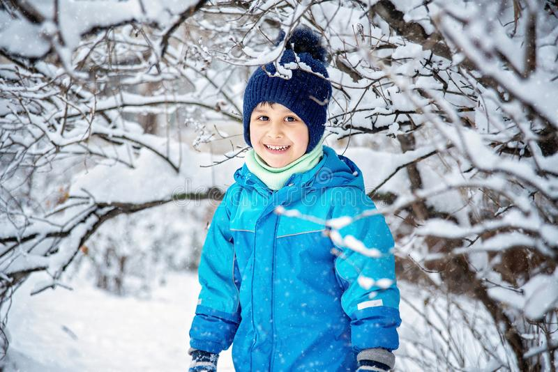 Boy in snow in Park. boy plays in winter wood. Adorable child having fun in winter park. playing outdoors with snow. Childhood christmas holiday nature toddler royalty free stock images
