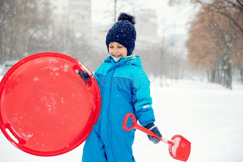 Boy in snow in Park. boy plays in winter wood. Adorable child having fun in winter park. playing outdoors with snow. Funny little boy playing with snow. child royalty free stock image