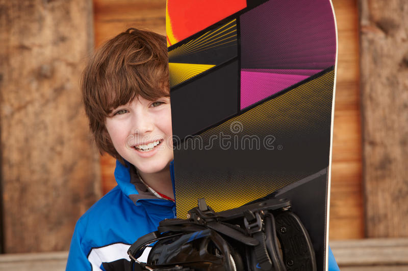 Boy With Snowboard On Ski Holiday royalty free stock image