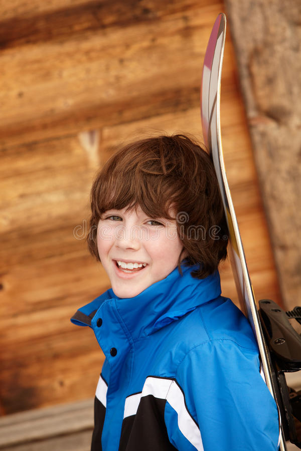 Boy With Snowboard On Ski Holiday royalty free stock images
