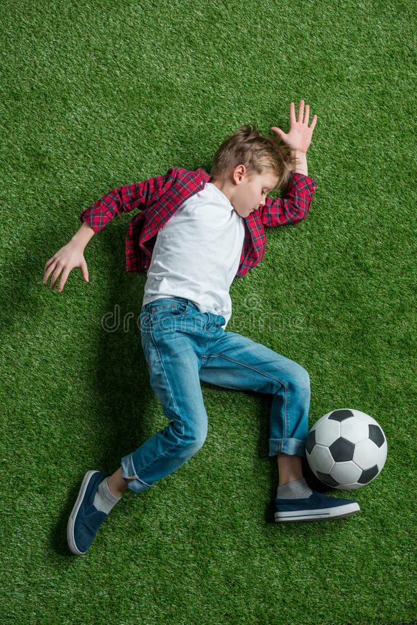 Boy with soccer ball lying on green grass royalty free stock photos