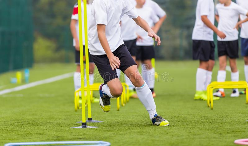 Boy Soccer Player In Training. Boy Running Between Cones During Practice in Field. On Sunny Day. Young Soccer Players at Speed and Agility Practice Session royalty free stock photo