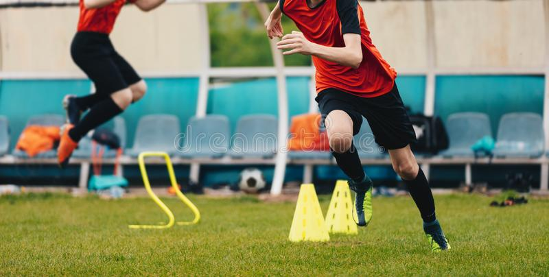 Boy Soccer Player In Training. Boys Running Between Cones amd Jumping During Practice in Field on Sunny Day. Young Soccer Players. Boy Soccer Player In Training royalty free stock photos
