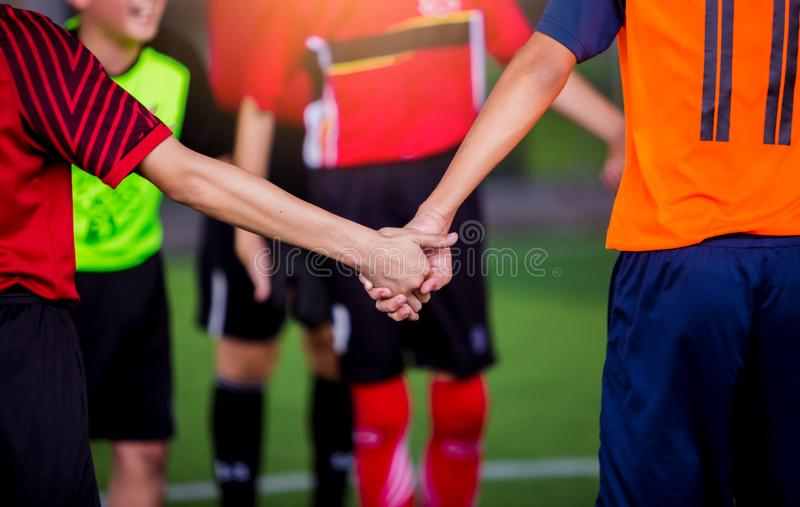 Boy soccer players tap hands together for football training. Soccer players and goalkeeper training speed hand together royalty free stock images