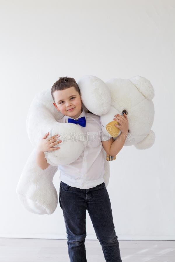 Boy with a soft toy of a large bear royalty free stock images