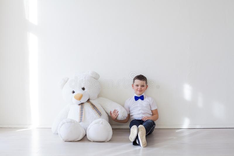 Boy with a soft toy of a large bear royalty free stock image