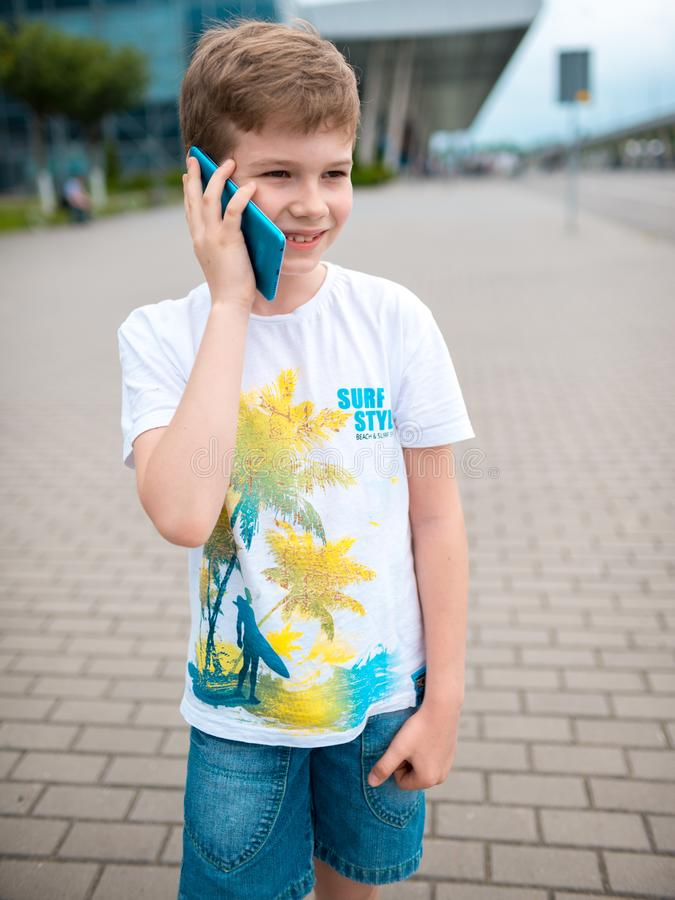 The boy speaks by phone. plays the game stock photography