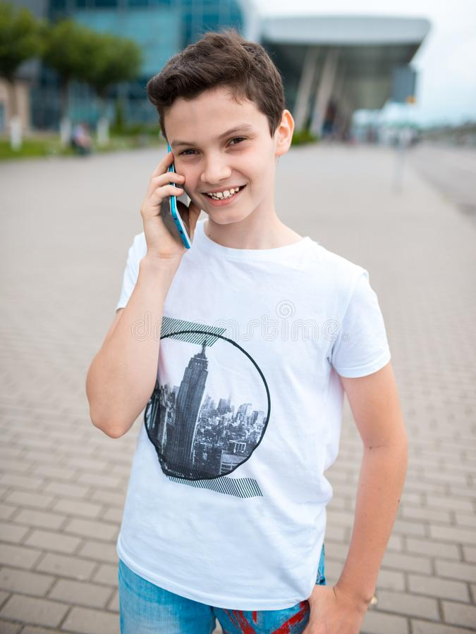 The boy speaks by phone. plays the game royalty free stock photo