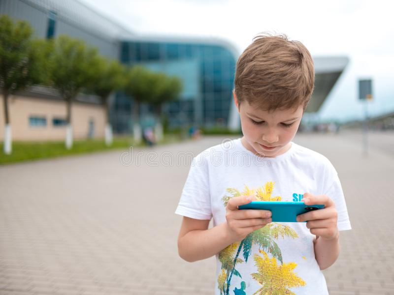 The boy speaks by phone. plays the game stock photos