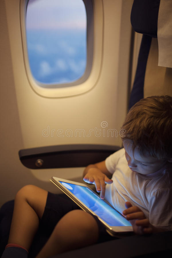 Boy spending time with tablet PC during flight stock photos