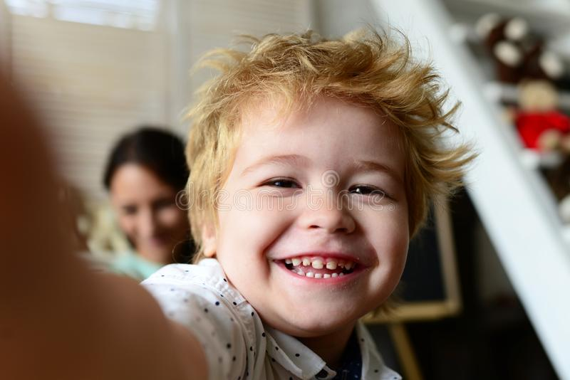 Boy spends fun time in playroom. Child with cheerful face. And blond hair, close up. Joy and games concept. Kid with his mother on light room background stock photography