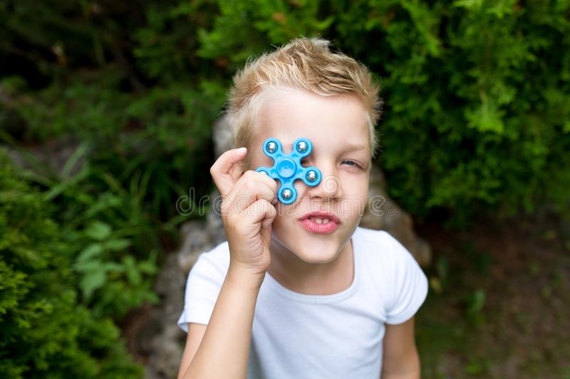 Boy with spinner. The boy is holding new fashionable toy fidget-spinner, hand-spinner stock photo