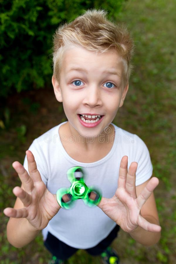 Boy with spinner. The boy is holding new fashionable toy fidget-spinner, hand-spinner royalty free stock image