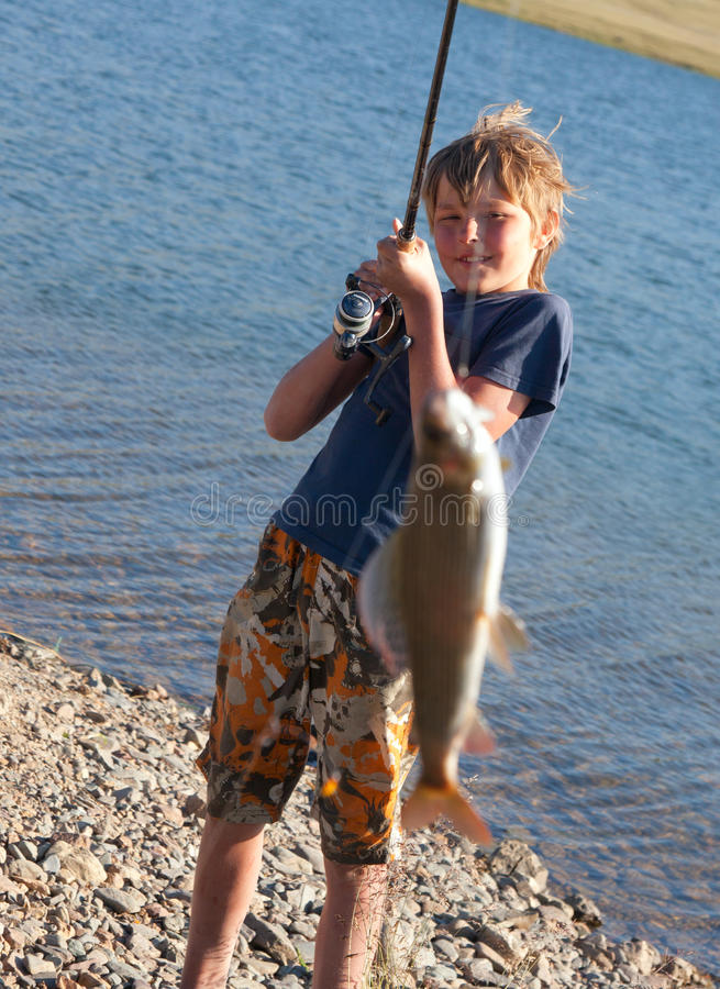 The boy with a spinning catch grayling stock photography