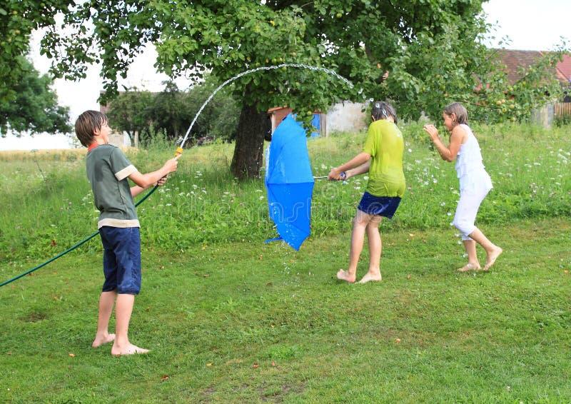 Boy splashing another kids with garden hose royalty free stock photos