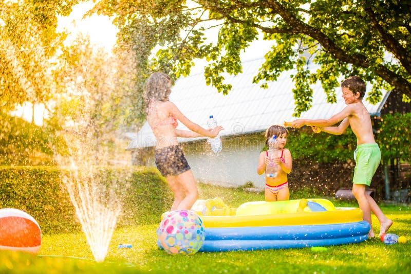Boy splashing girls with water gun in the garden royalty free stock images