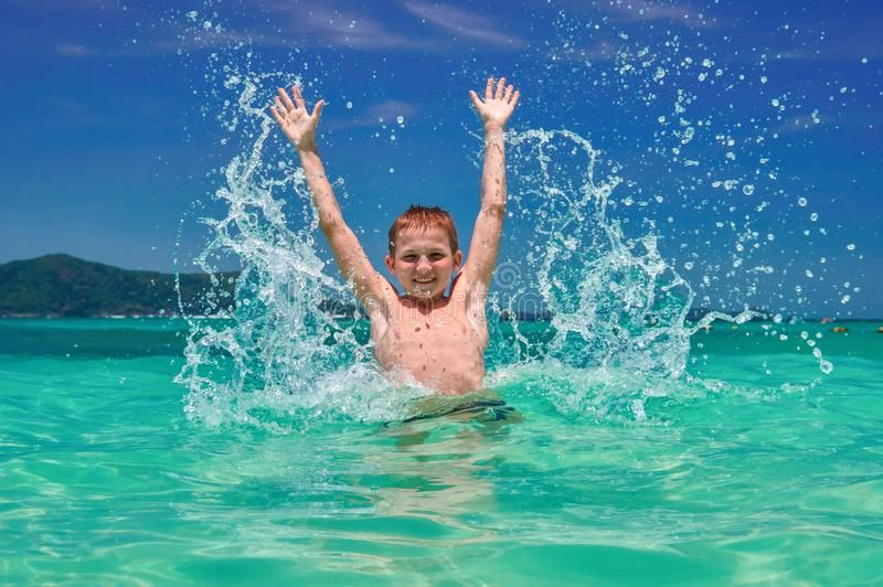 Boy splashing water in sea. Playful child 10 years old surrounded by colorful nature. Bright blue sky and shimmering sea. stock photography