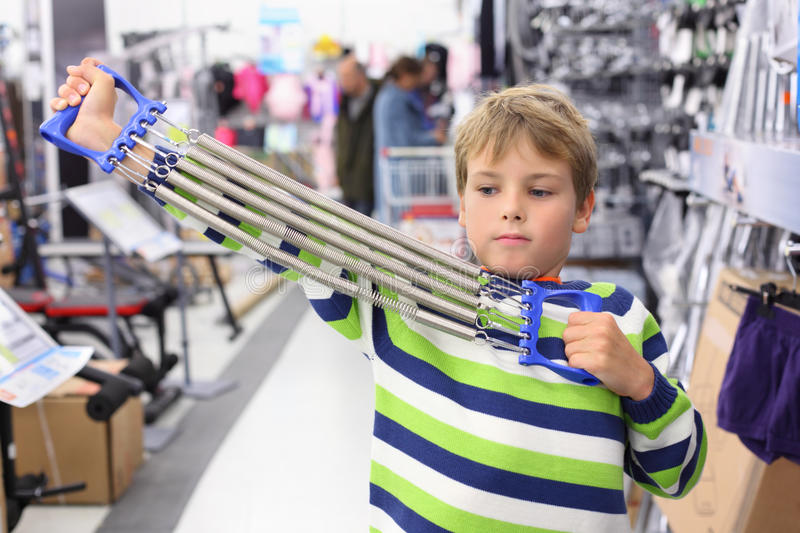 Boy in sports shop tries metal shoulder expander. With springs royalty free stock image