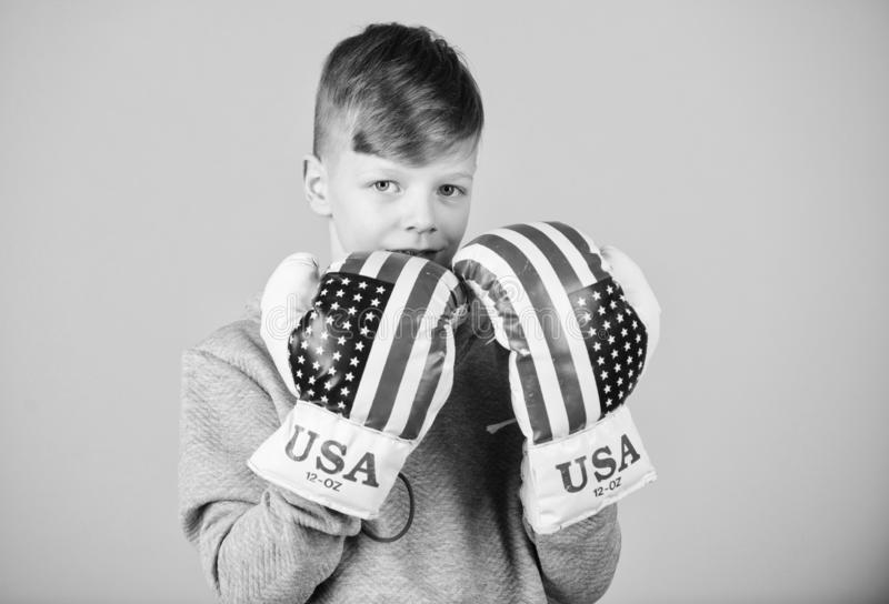 Boy sportsman wear boxing gloves with usa flag. Start boxing career. American boxer concept. Child sporty athlete. Practicing boxing skills. Boxing sport royalty free stock image