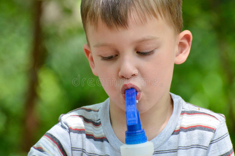 A boy and a spray bottle. A four year old boy sucks water out of a spray bottle stock photos