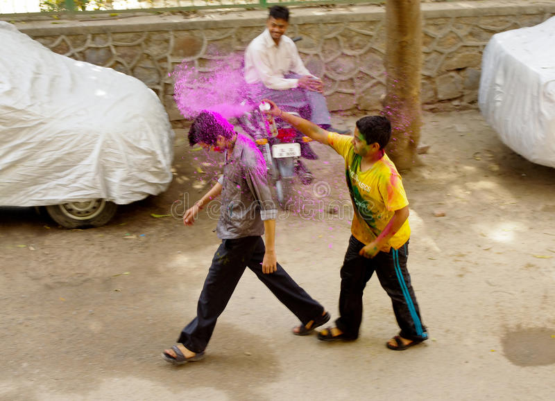 Boy spraying paint for Holi. Indian boy spraying a passerby to celebrate Holi, festival of colours, New Delhi, India stock photography