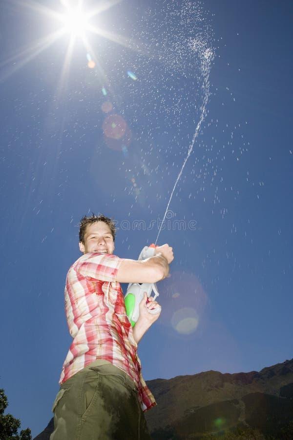 Boy Spraying Water From Gun Into Air. Portrait of teenage boy spraying water from gun into air stock image