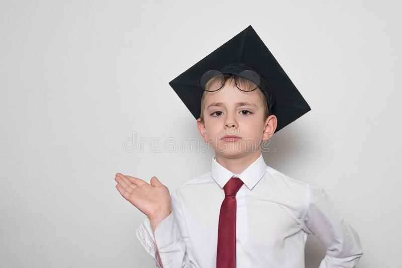 Boy in a square academic hat and glasses holds his palm up. School concept. White background.  stock photo