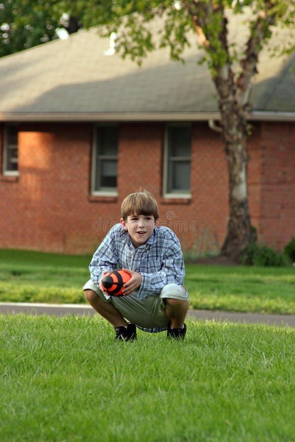 Boy Squatting Holding Football. Boy holding football quatting down royalty free stock photo