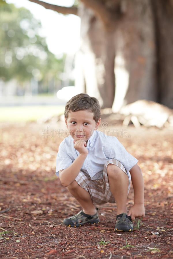 Boy squatting in the park stock photography