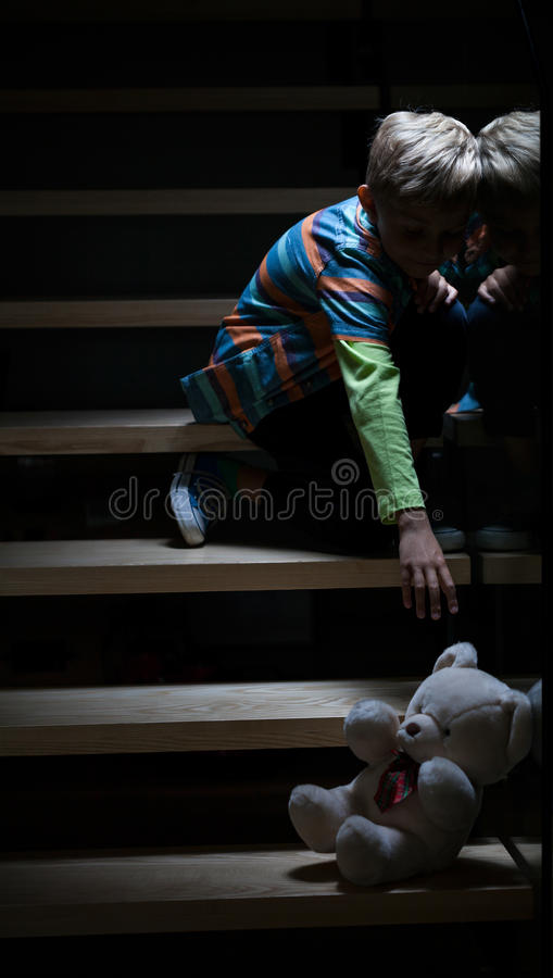 Boy on stairs at night royalty free stock photo