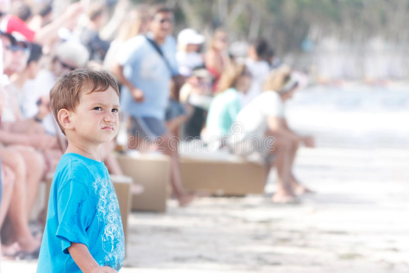 Boy standing alone on fan crowd background royalty free stock image