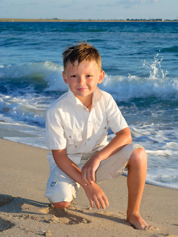Boy standing at the beach stock photos
