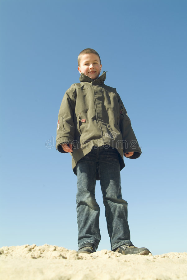 Boy standing at the beach, looking down stock images