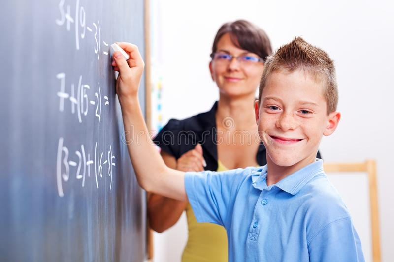 Boy standing on chalkboard in front of teacher royalty free stock photos