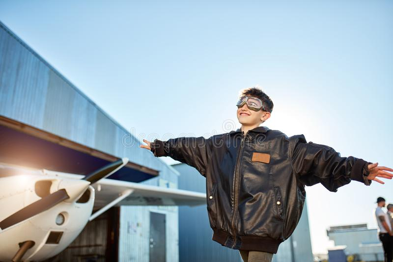 Boy standing with hands apart like plane wings, dressed in pilot jacket and aviator glasses stock photography